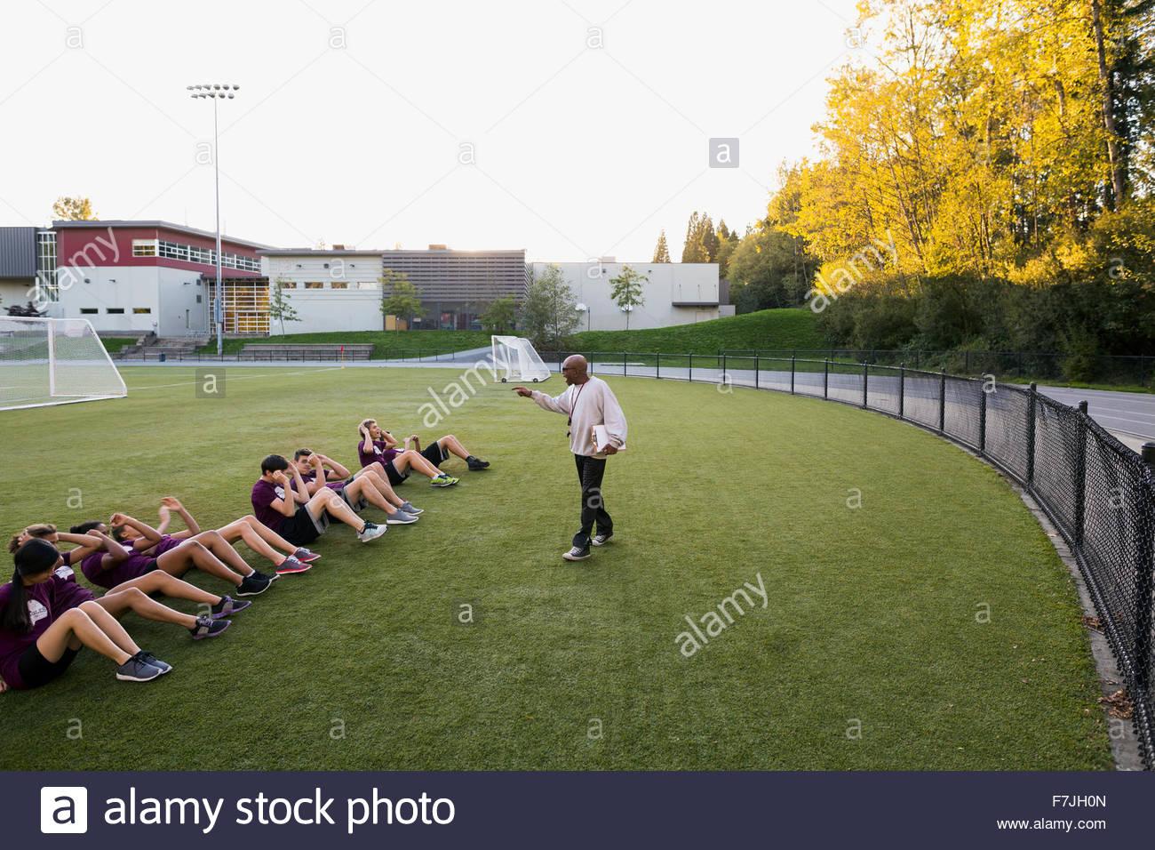 High School Leibeserziehung Lehrer Schüler Sit-ups Stockbild