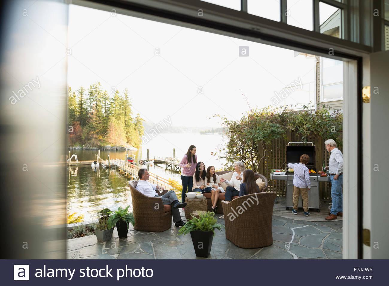 Mehr-Generationen-Familie grillen und entspannende Terrasse am See Stockbild