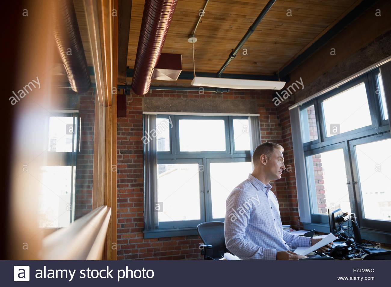 Geschäftsmann mit Papierkram im Büro Stockbild