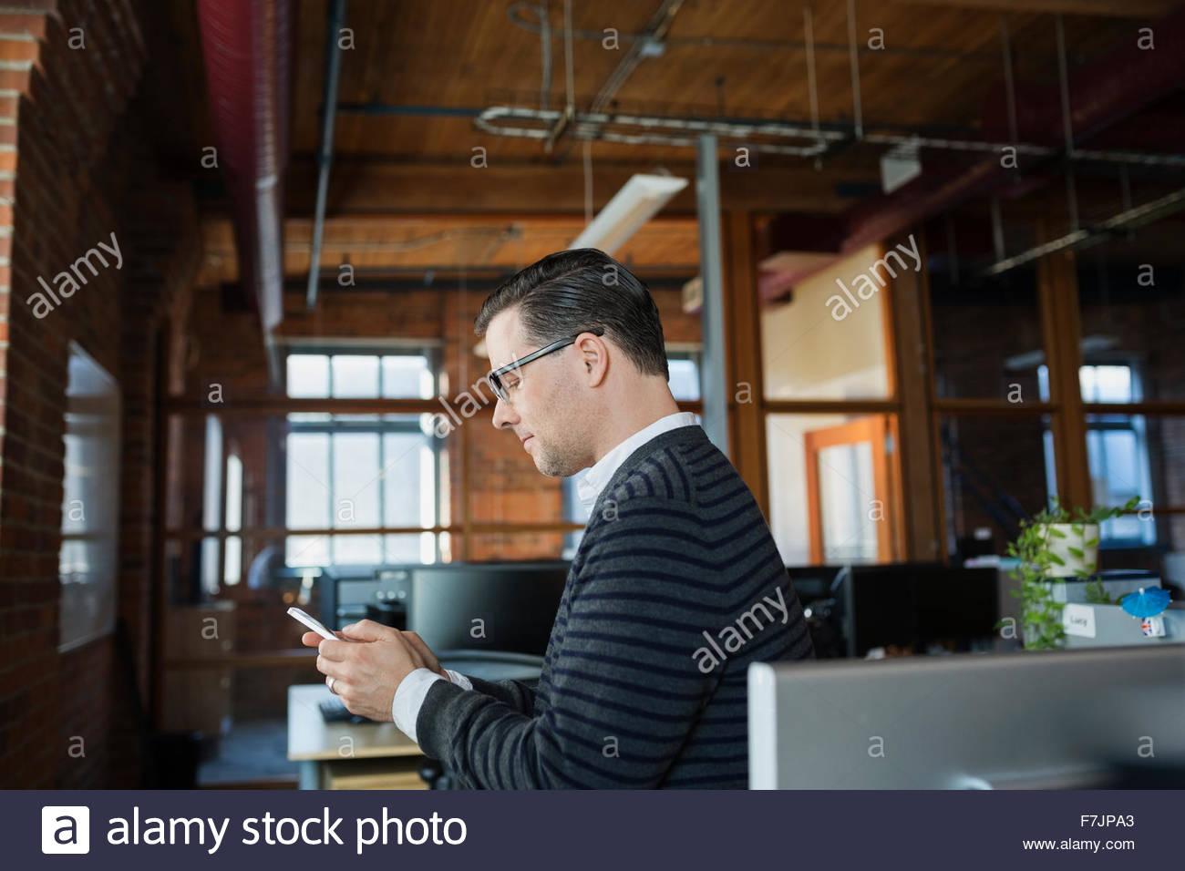 Geschäftsmann SMS im Büro Stockbild