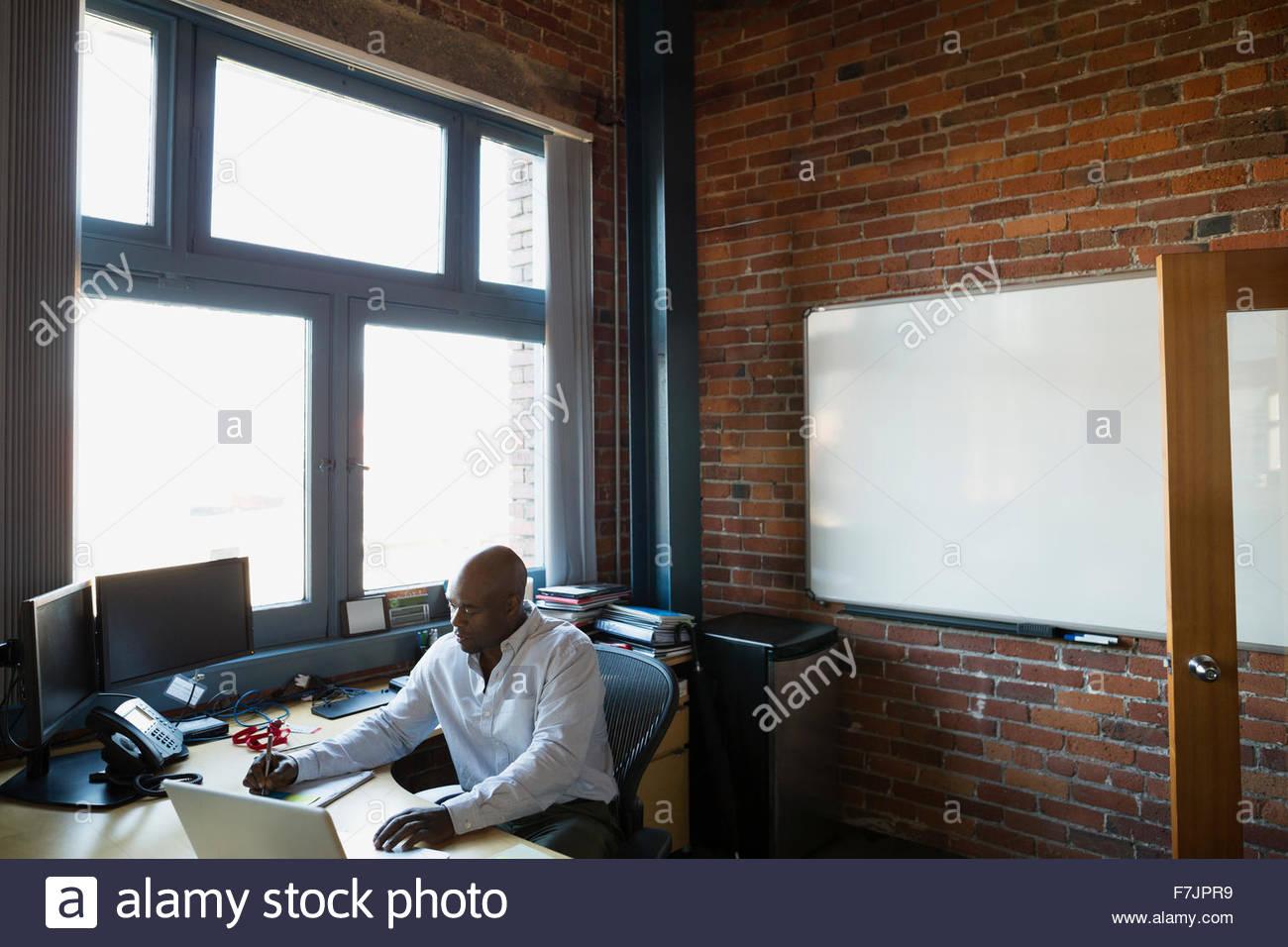 Geschäftsmann, arbeiten am Laptop am Schreibtisch Stockbild