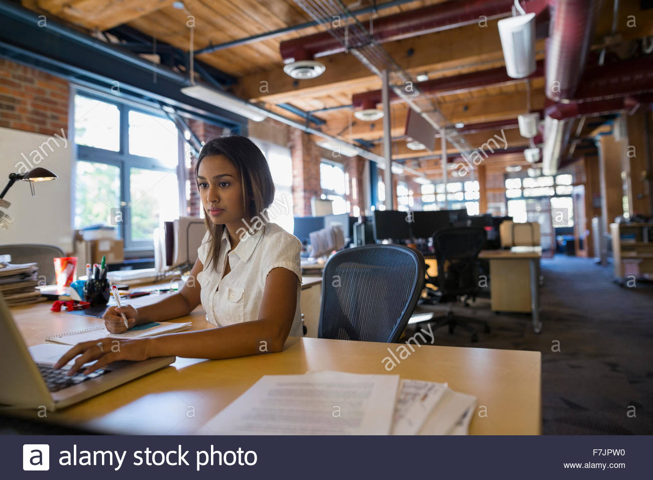 Geschäftsfrau, die Arbeiten am Laptop am Schreibtisch Stockbild