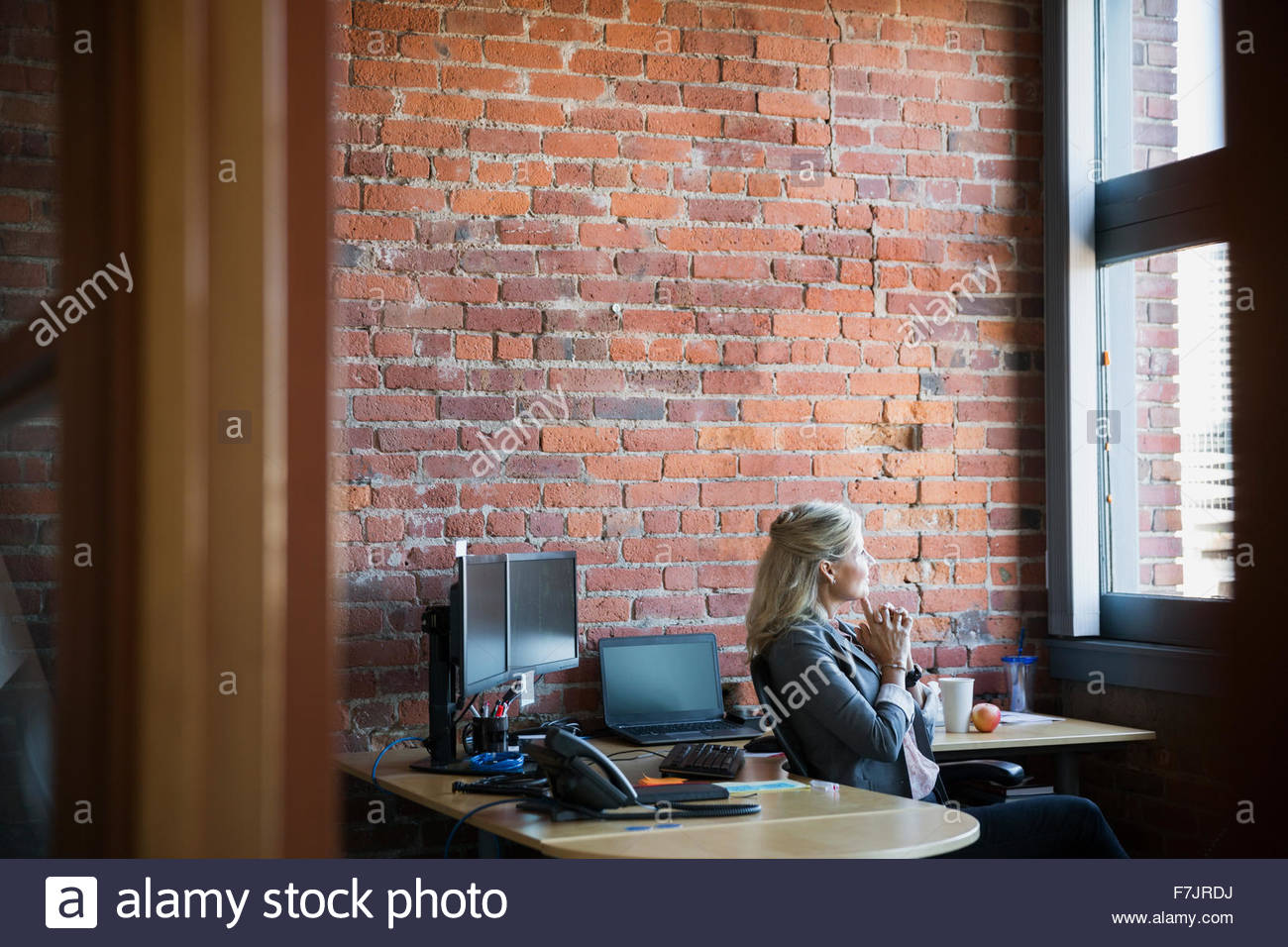 Nachdenklich schaut Bürofenster Geschäftsfrau Stockbild