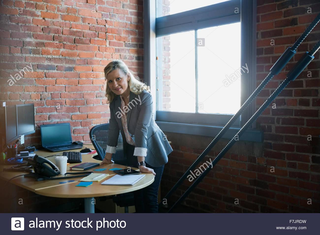 Porträt zuversichtlich Geschäftsfrau stützte sich auf Schreibtisch Stockbild
