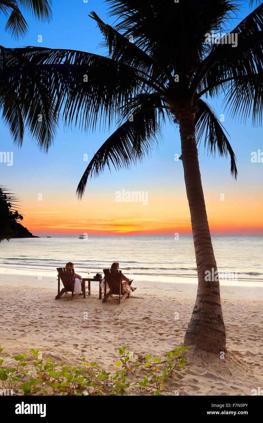 Touristen am tropischen Strand nach Sonnenuntergang, Insel Koh Samet, Thailand Stockbild