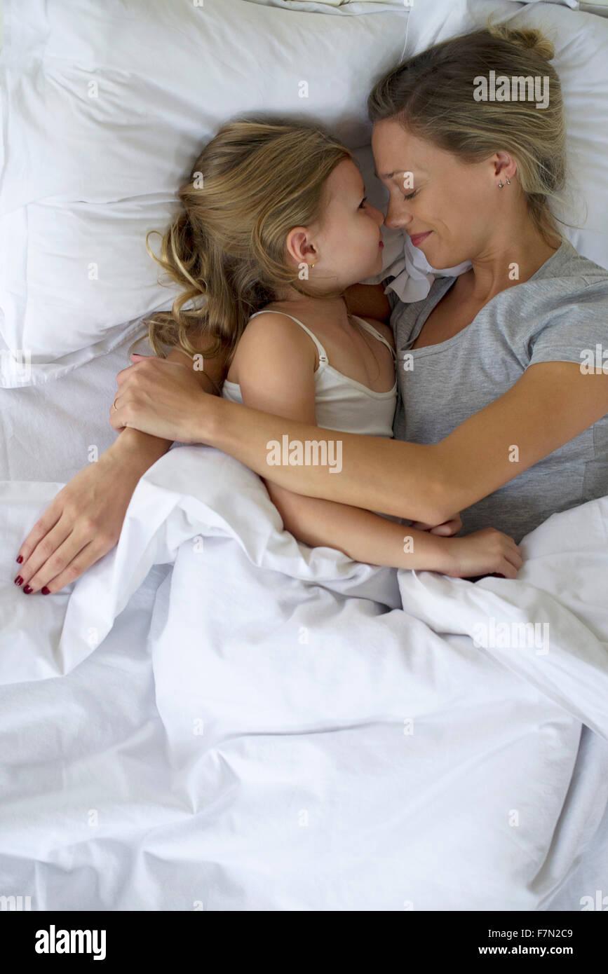 Mutter und Tochter im Bett umarmt Stockbild