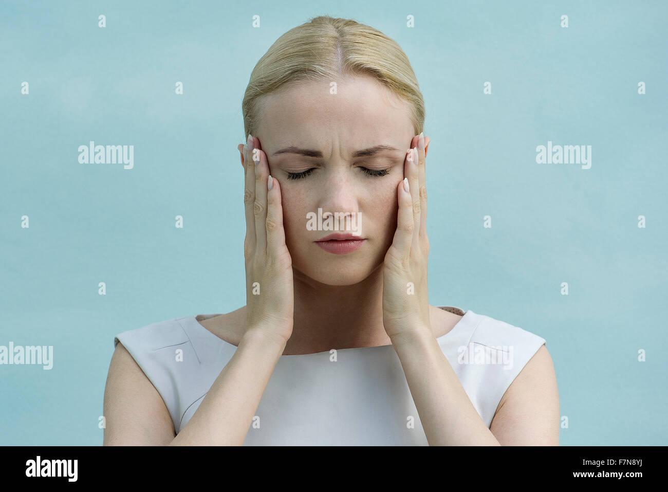 Frau mit Gesicht in Händen, Augen geschlossen Stockbild