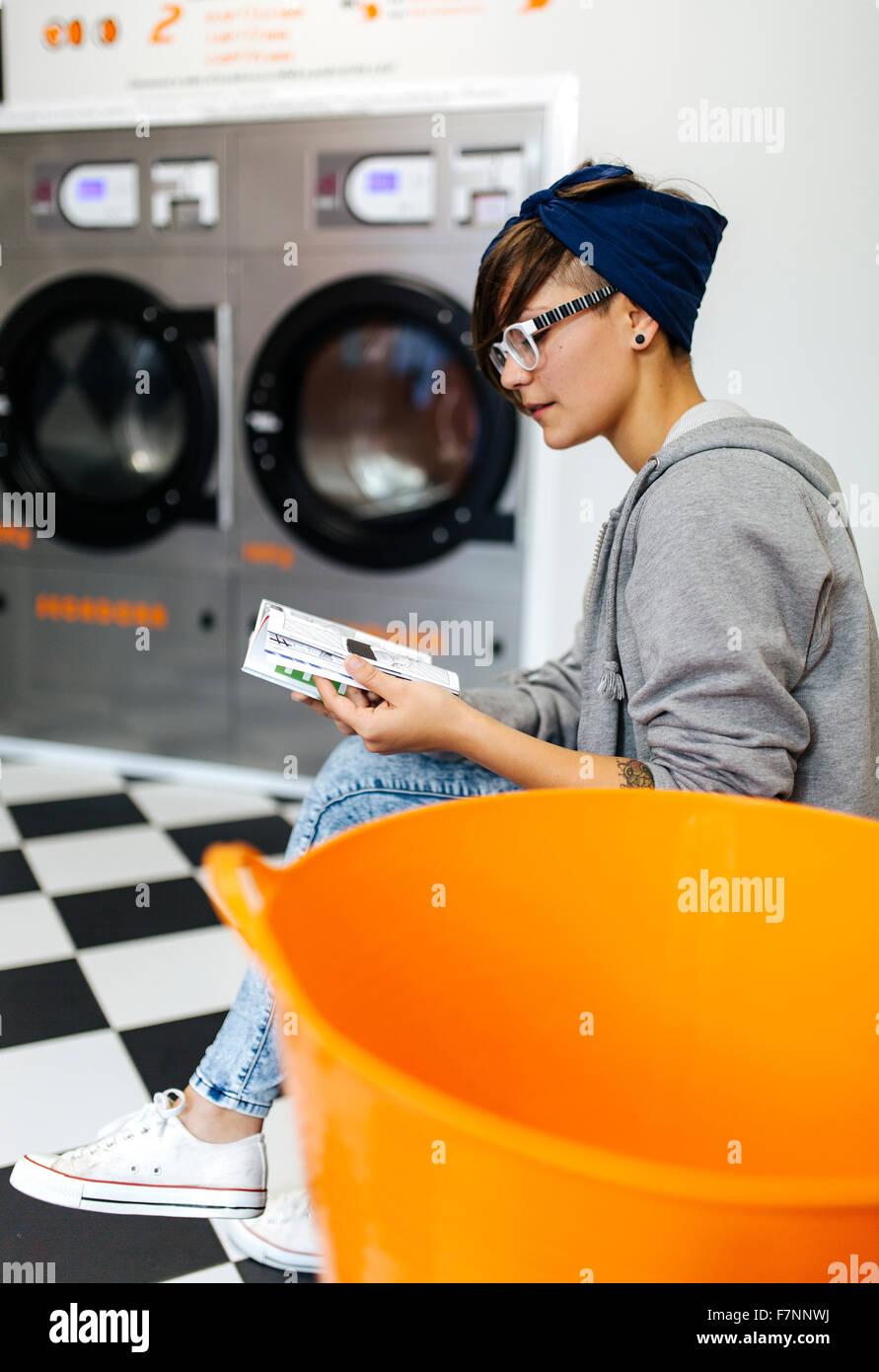 Junge Frau liest Comic-Strip in einen Waschsalon Stockbild