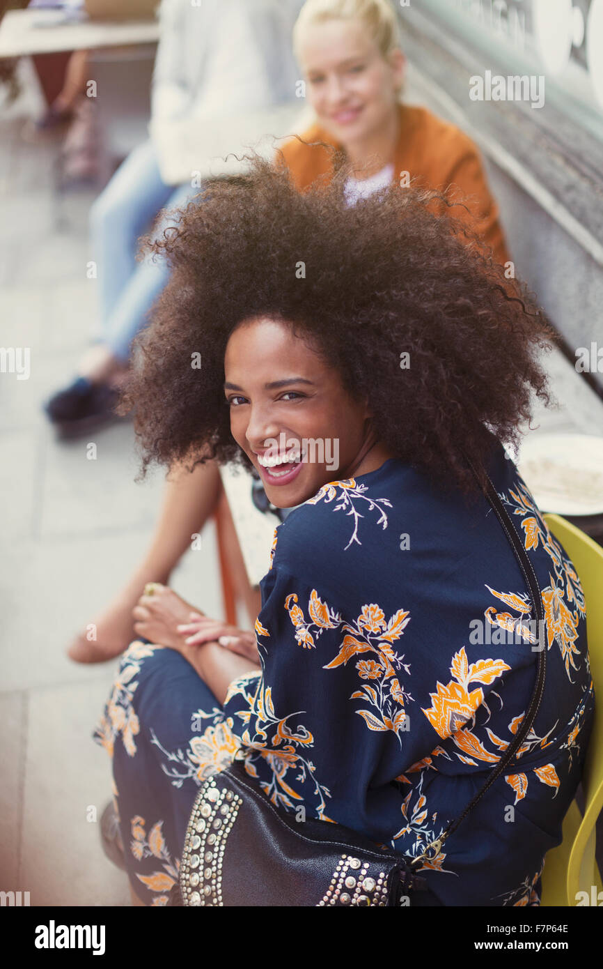 Porträt begeistert Frau mit Afro am Straßencafé Stockfoto