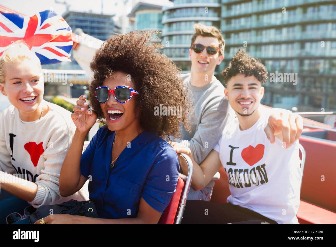Porträt begeisterte Freunde mit britischer Flagge fahren Doppeldecker-bus Stockbild