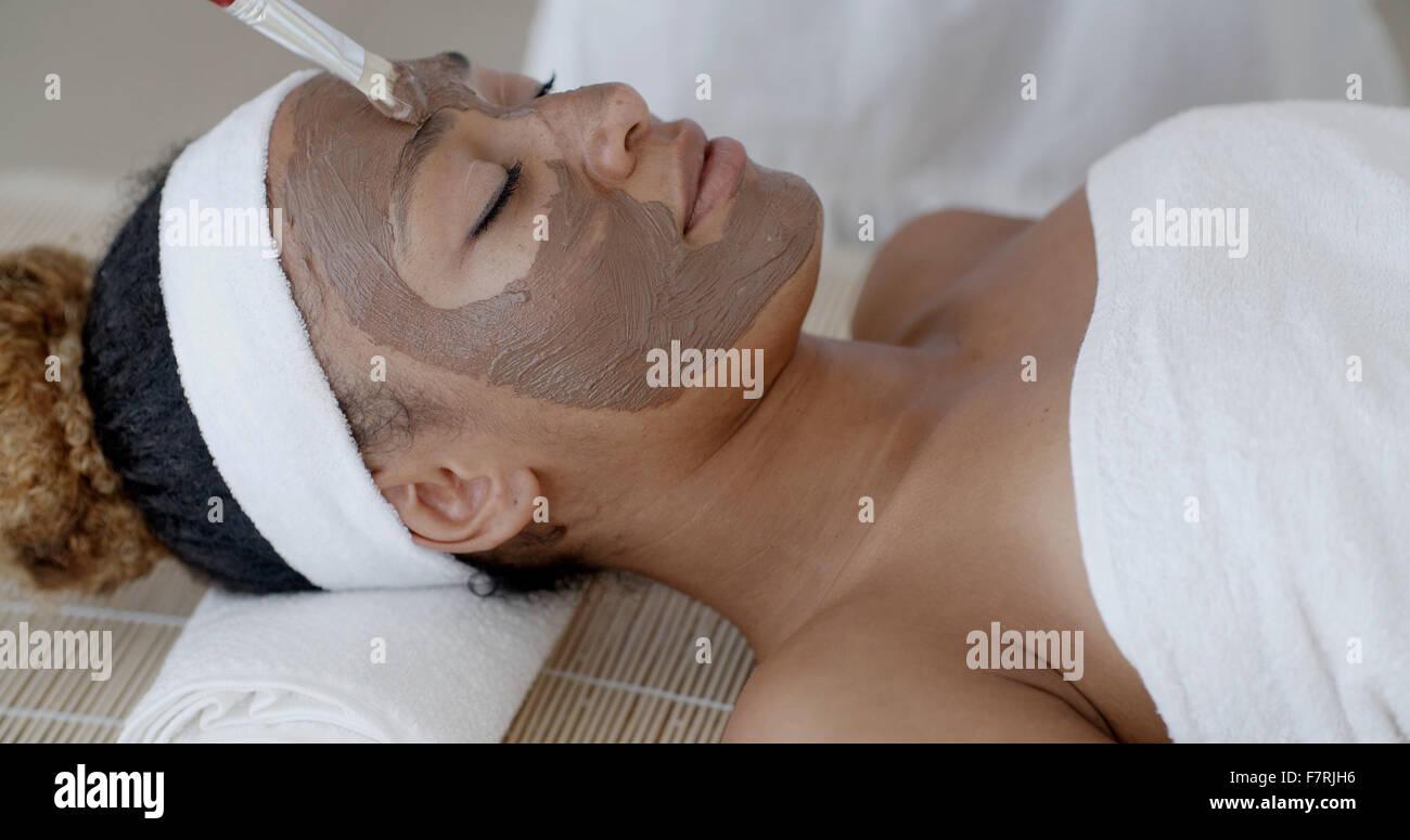 Frau mit Clay Facial Mask In Spa Stockbild