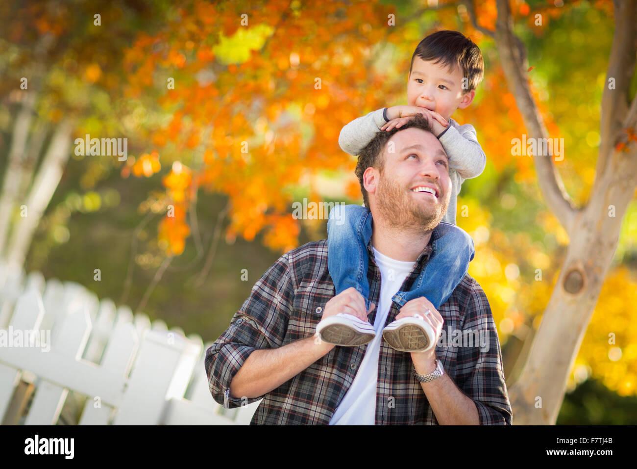 Happy Mixed Race junge Reiten Huckepack auf den Schultern der kaukasischen Vater. Stockbild