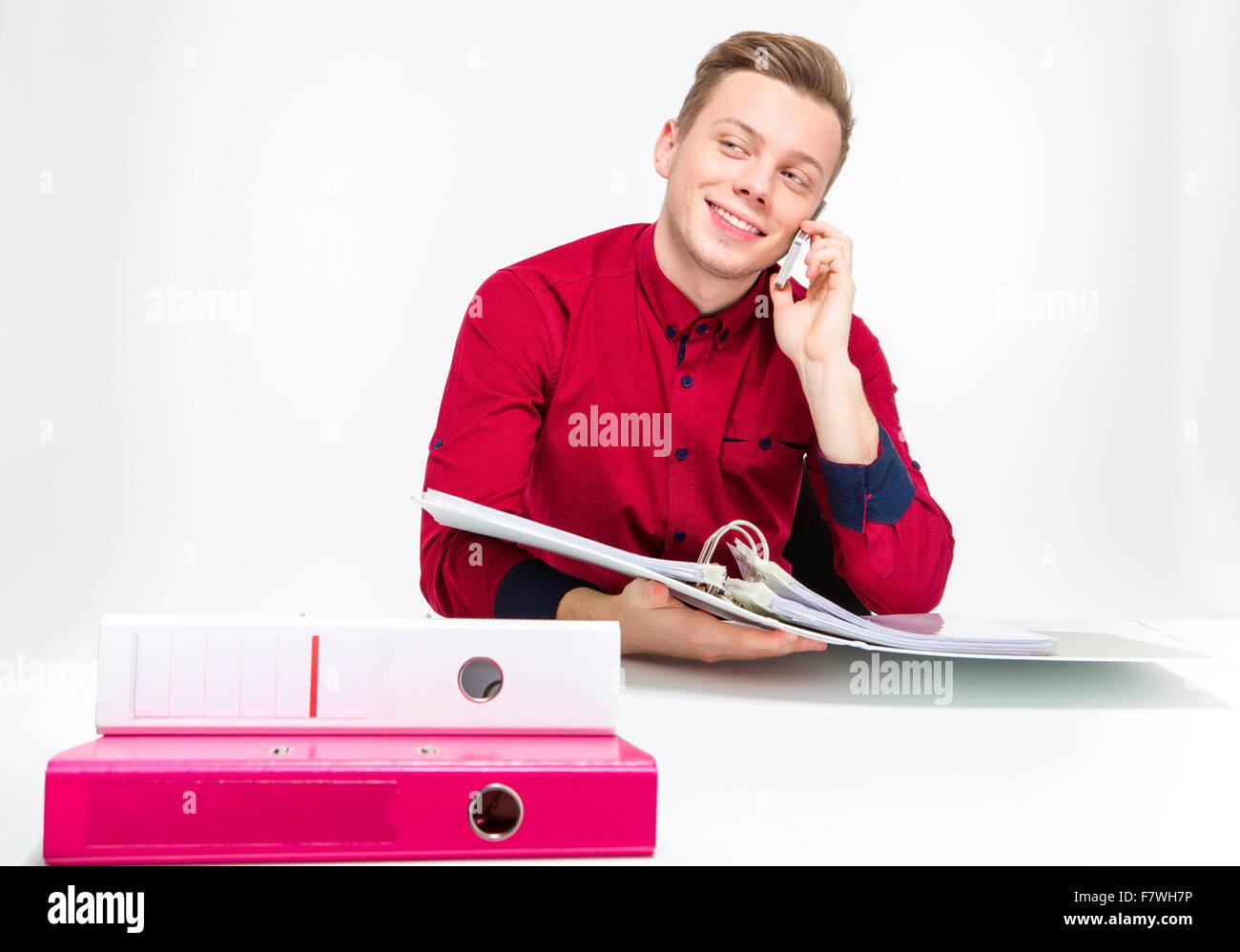 Verspielt fröhlich attraktive junge Mann im roten Hemd mit Bindemitteln und Gespräch am Handy auf weißem Stockbild