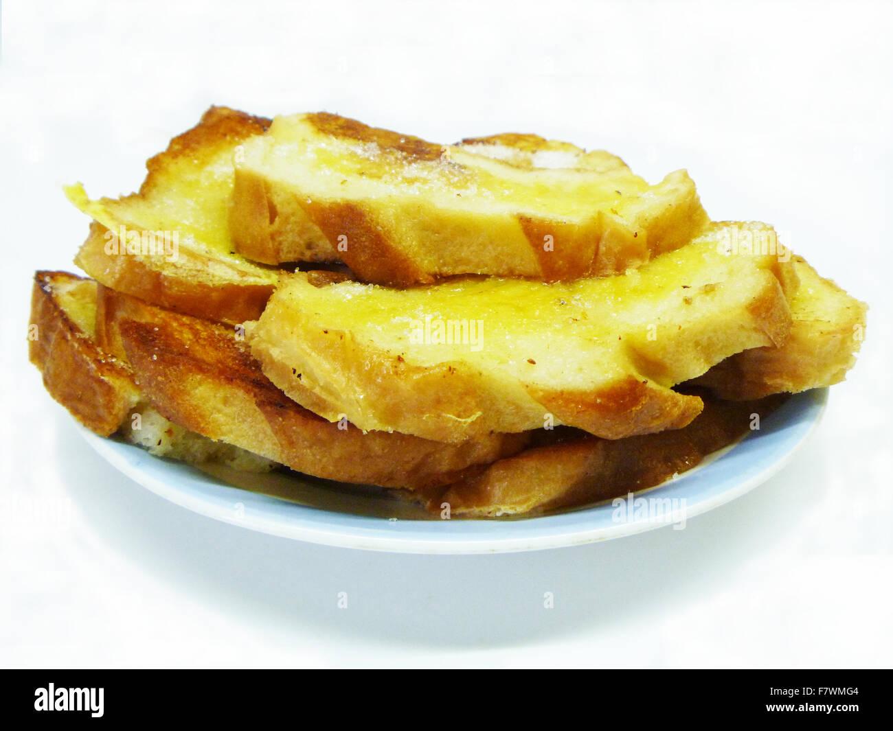 Brot auf Teller ist auf hellem Hintergrund isoliert. Stockbild
