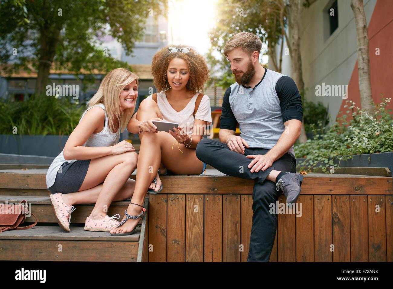 Im Freien Schuss Gruppe von jungen Erwachsenen Handy betrachten. Junge Freunde mit Handy. Stockbild