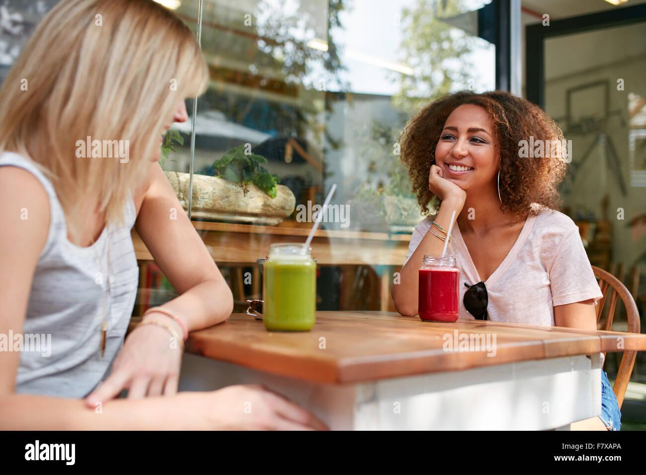 Bild der jungen afrikanischen Mädchen sitzt mit ihrer Freundin im Café im Freien. Zwei junge Frauen treffen Stockbild