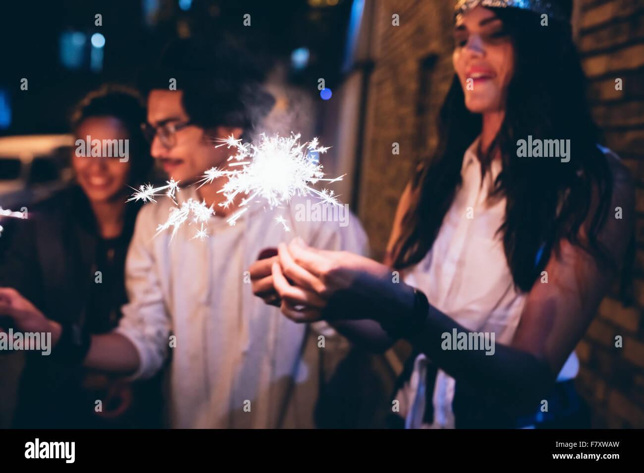 Junge Freunde, der in der Nacht feiert mit Wunderkerzen. Männer und Frauen hängen am Abend eine Party. Stockbild