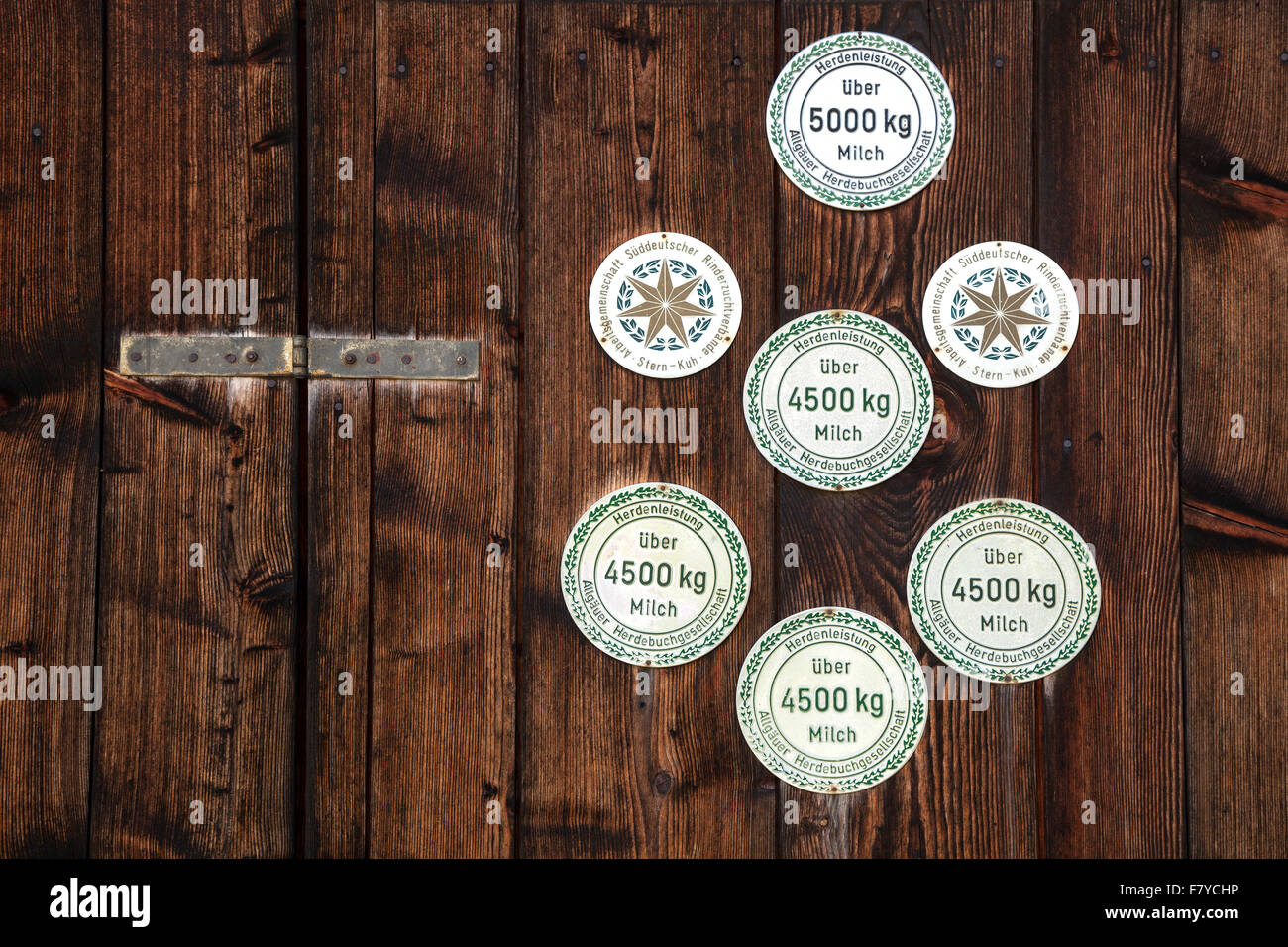Plaketten für die Milchleistung der Kühe auf einer Scheune in Bruck, Allgäu, Bayern, Deutschland Stockbild