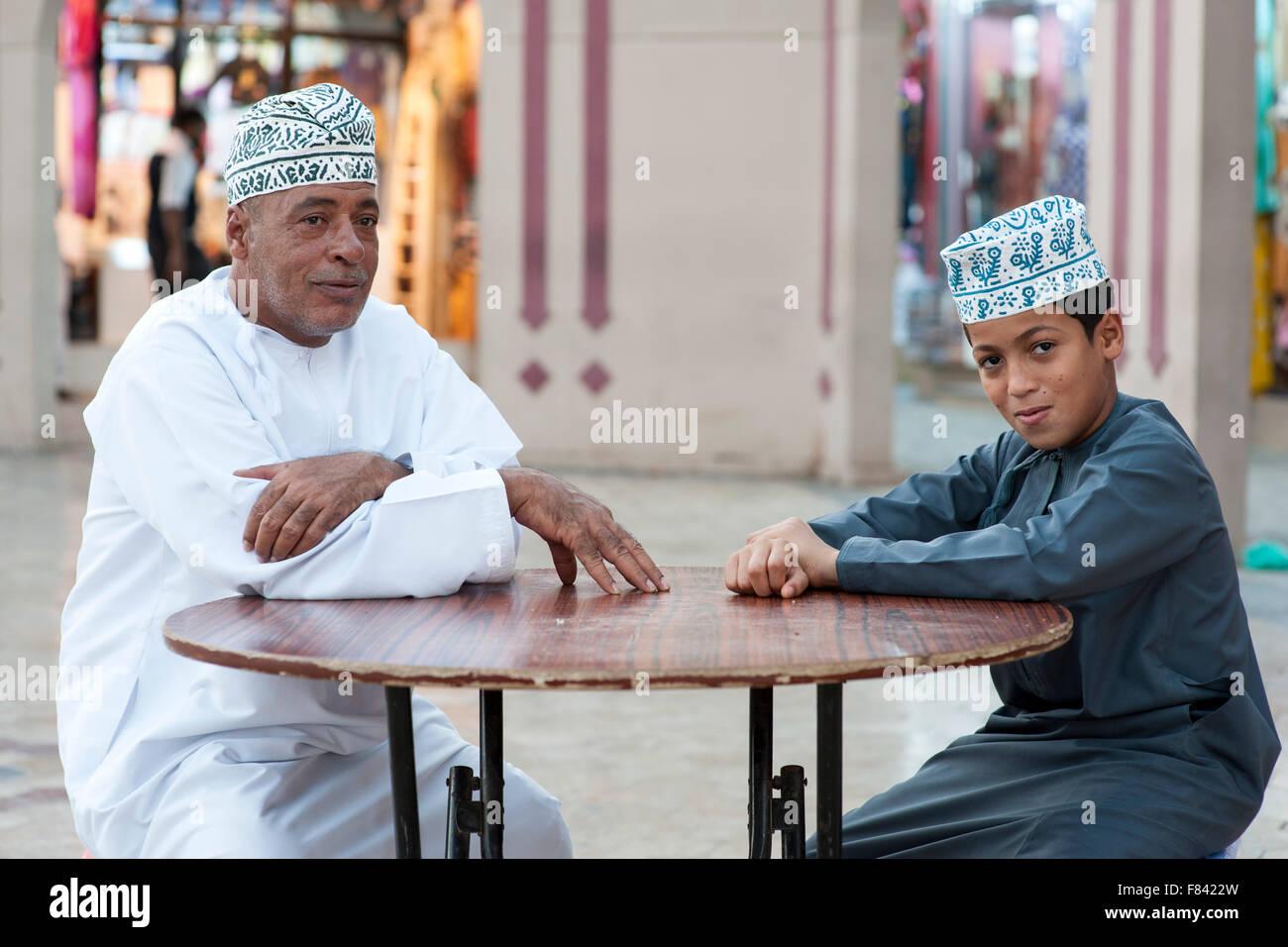 Omanische Mann und sein Sohn sitzen außerhalb des Mutrah Souks in Muscat, der Hauptstadt des Sultanats Oman. Stockbild