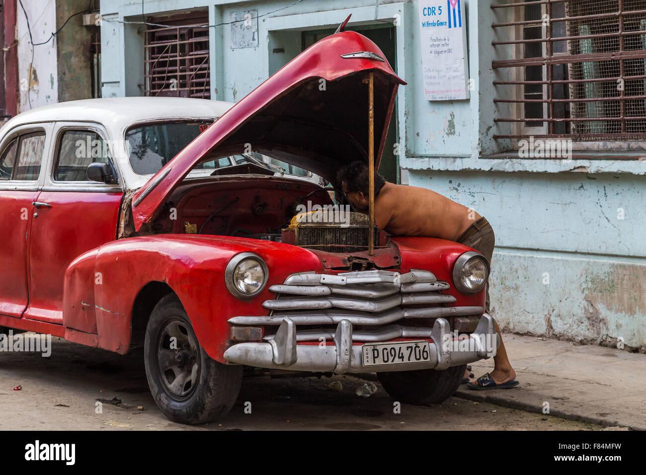 Ein Mann, immer unter der Motorhaube des seine Oldtimer in Havanna Centro. Stockbild