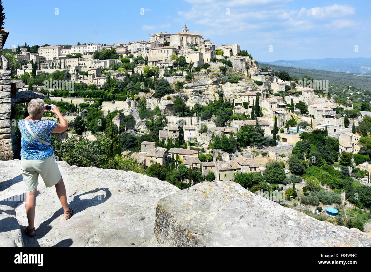 Gordes Hügel Dorf unfenced Aussichtsplattform mit Frau Touristen fotografieren Stockbild
