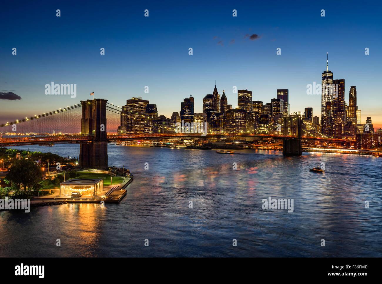 Brooklyn Bridge und beleuchtete Lower Manhattan in der Dämmerung. Financial District Wolkenkratzer reflektieren Stockbild