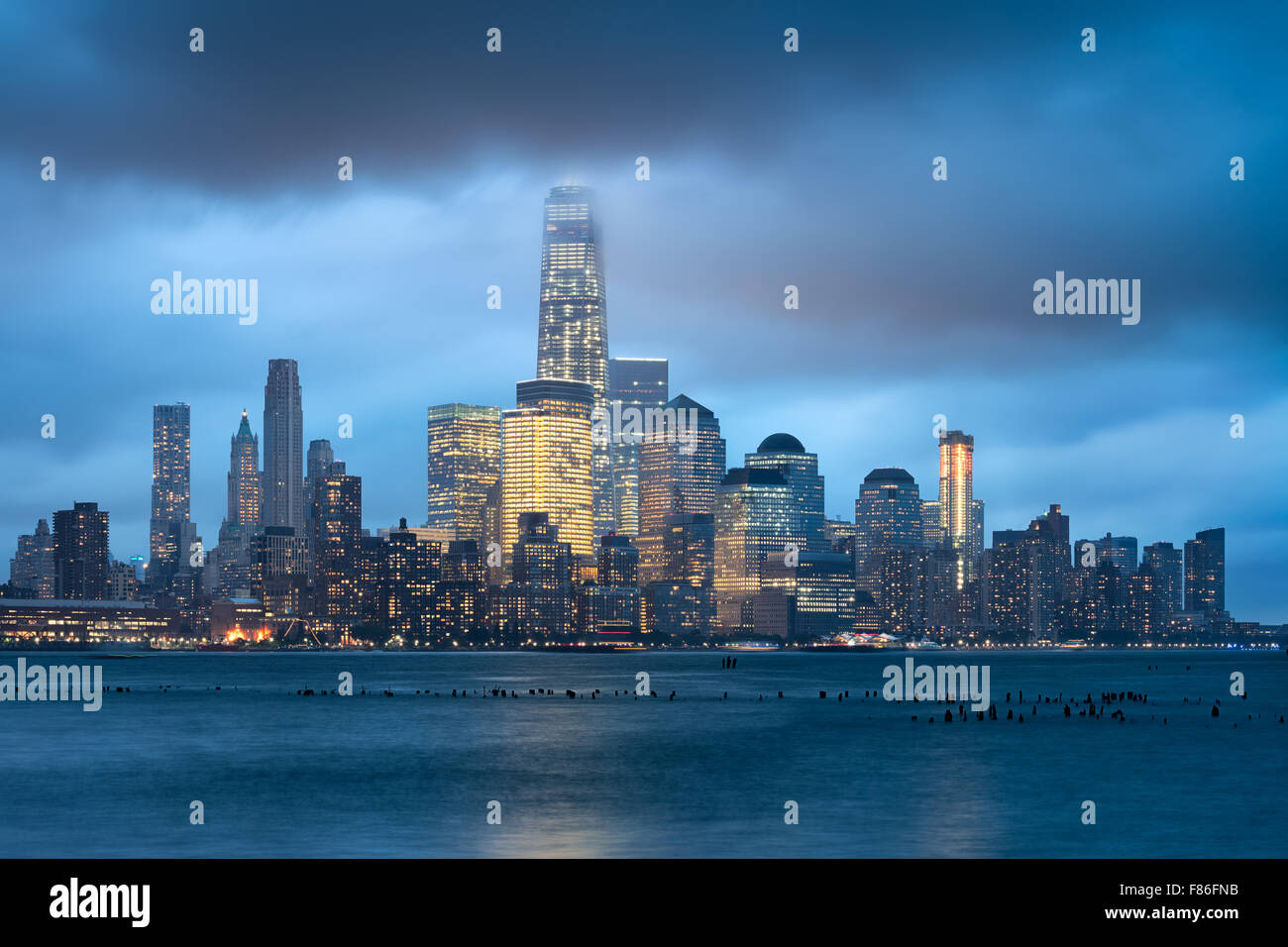 Lower Manhattan und Financial District beleuchtet Wolkenkratzer mit Gewitterwolken, New York City. World Trade Center Stockbild