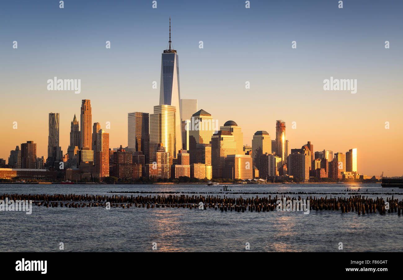 Lower Manhattan Financial District Wolkenkratzer bei Sonnenuntergang über Hudson River mit World Trade Center. Stockbild