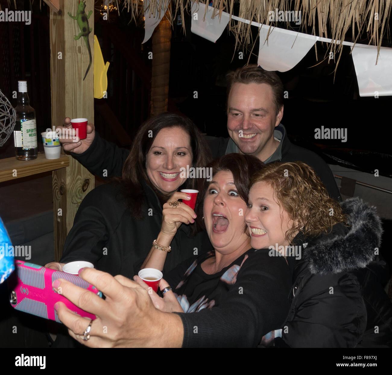 Familienmitglieder dabei, dass eine Handy Selfie einen Hinterhof Tiki Bar genießen. Downers Grove Illinois Stockbild