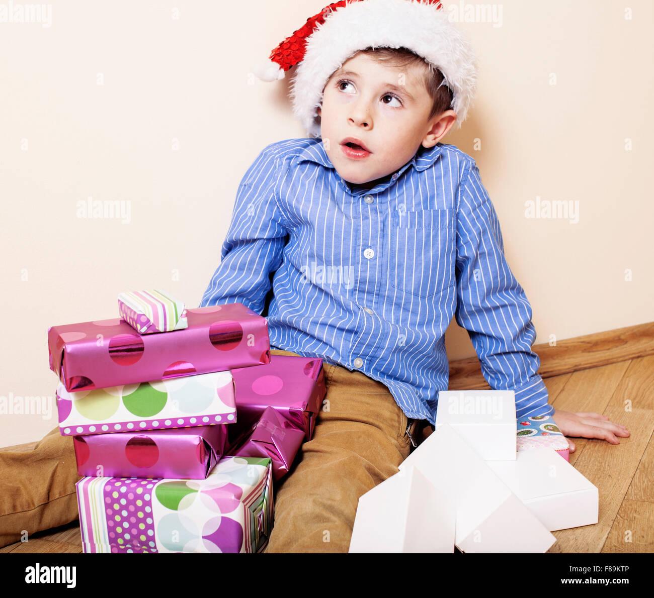 kleine niedliche Junge mit Weihnachtsgeschenken zu Hause. emotionale ...