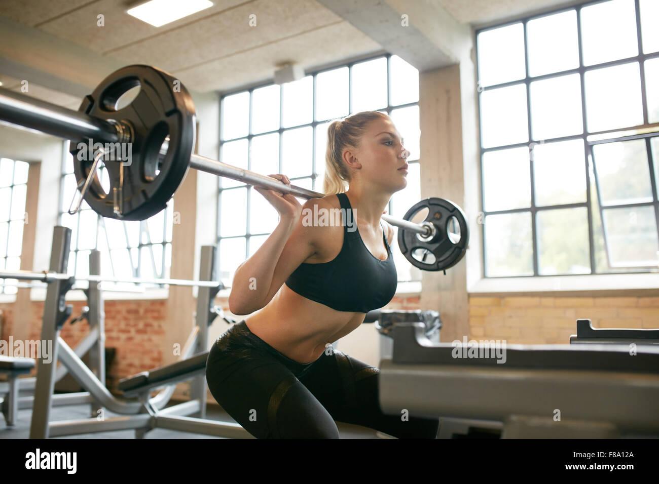 Weiblich, trainieren im Fitnessraum machen Kniebeugen mit Gewicht auf ihren Schultern. Junge Frau mit schweren Gewichten Stockbild
