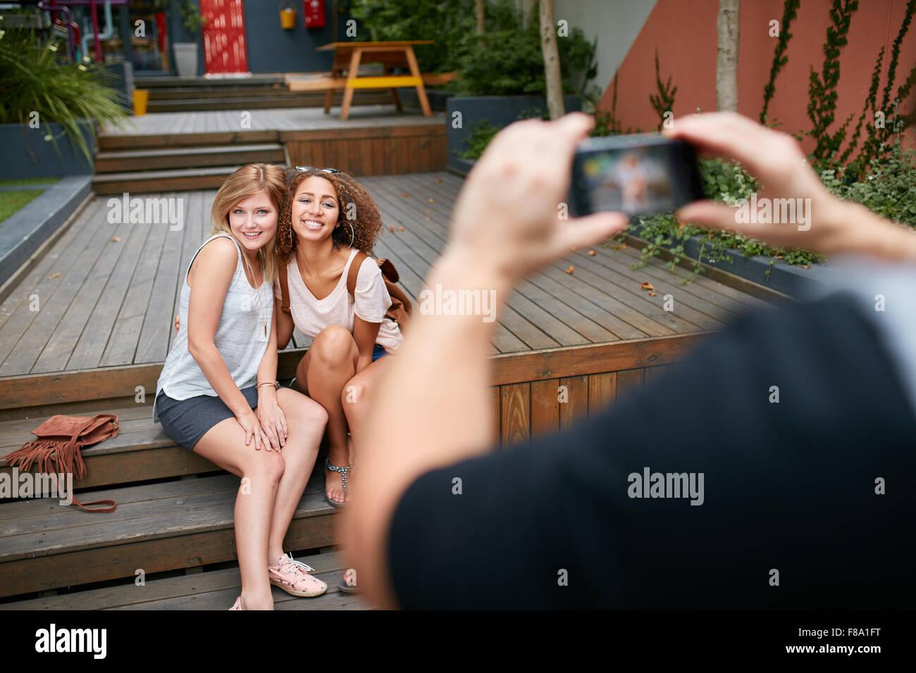 Zwei junge Frau sitzt zusammen posieren für ein Fotografieren ihres Freundes. Mann die Fotos seiner Freunde Stockbild