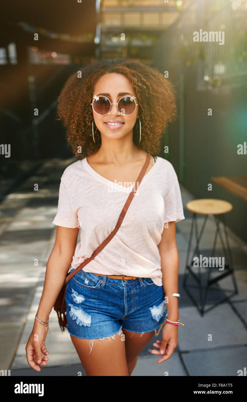Stilvolle afrikanische Frau mit Sonnenbrille posiert im Freien. Schöne junge Mädchen mit dem lockigen Stockbild