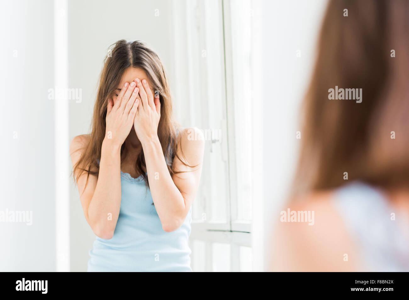 Frau verbirgt ihr Gesicht mit den Händen. Stockbild