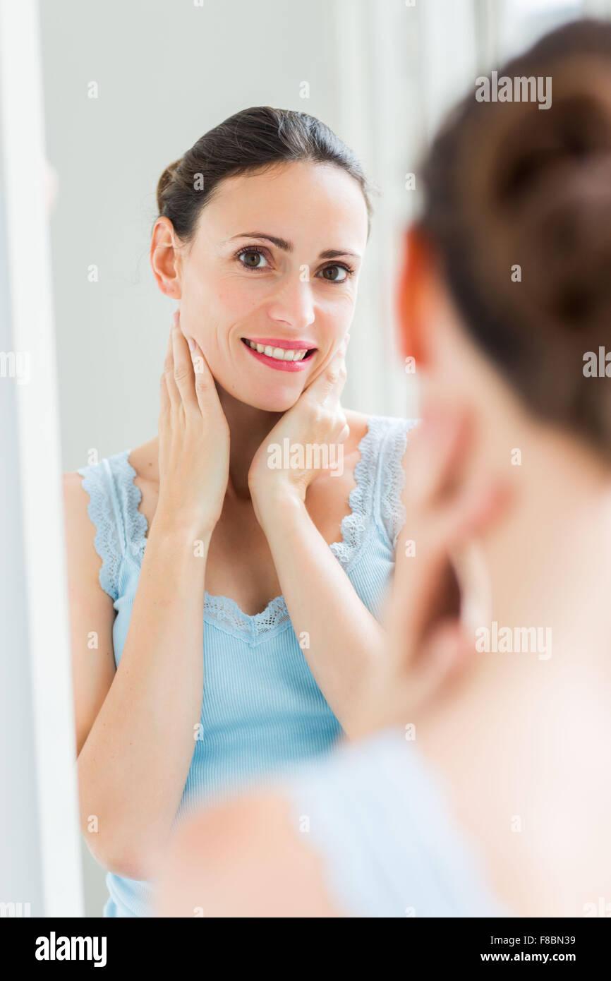 Frau ihr Gesicht im Spiegel zu überprüfen. Stockbild