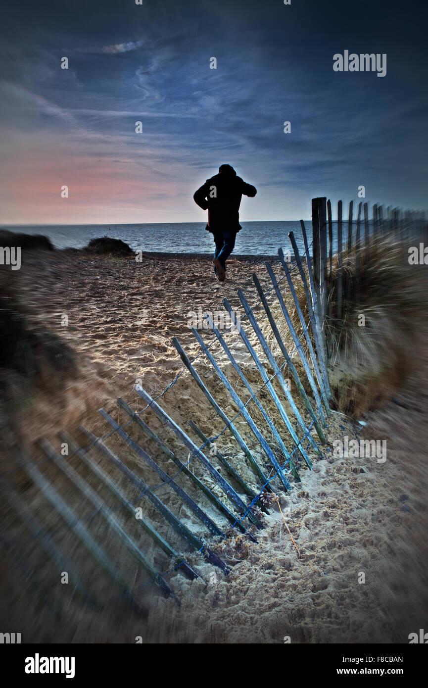 Mann läuft am Strand Stockbild
