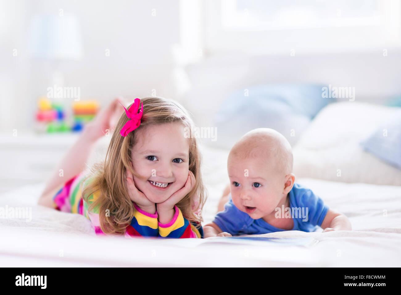 Bett Kleinkind Junge ~ Lustige happy kleinkind mädchen ein buch lesen und spielen mit