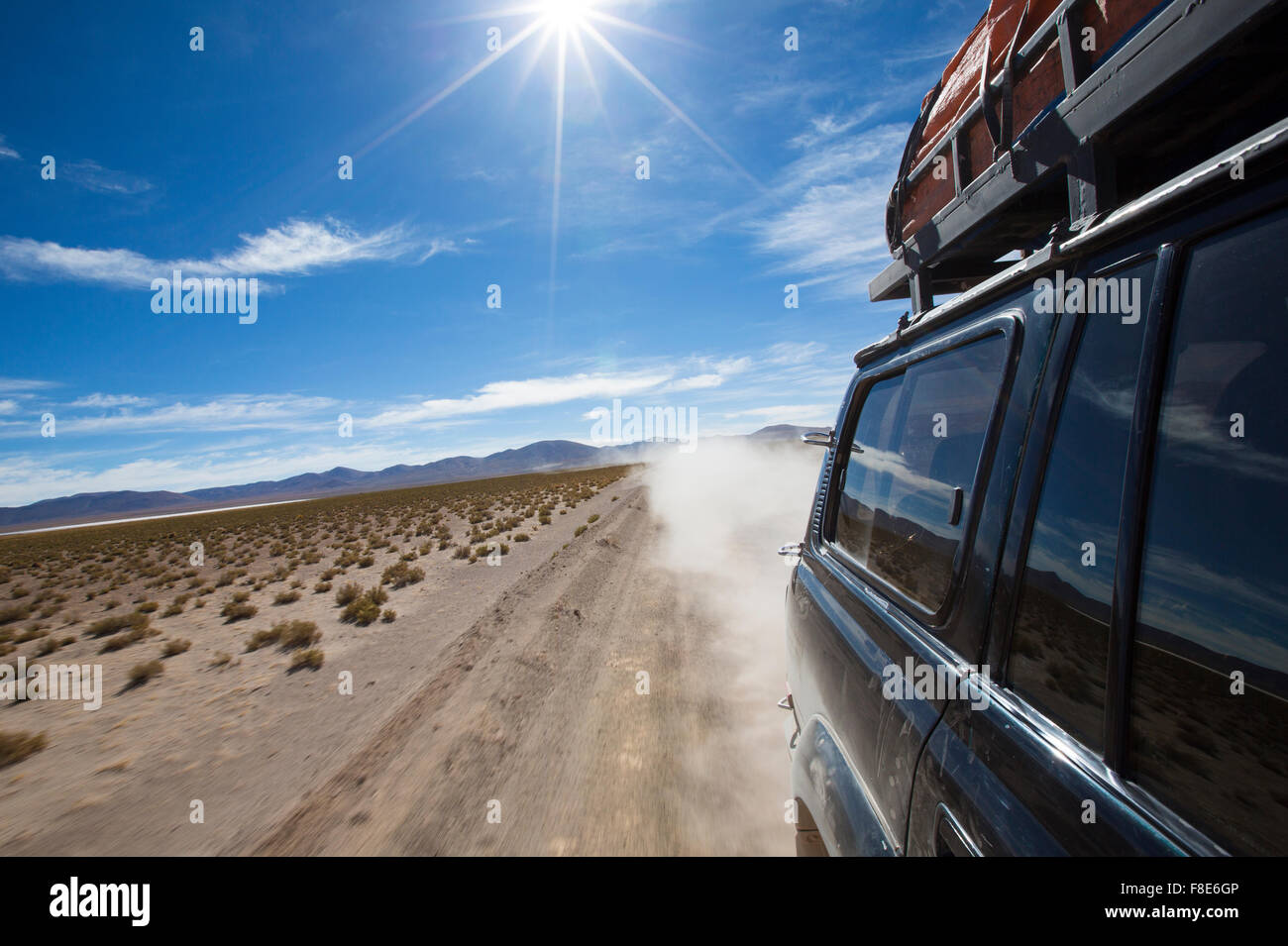 Off-Road-Fahrzeug fährt in der Atacama-Wüste, Bolivien mit Bergen und blauem Himmel in Eduardo Avaroa Stockbild