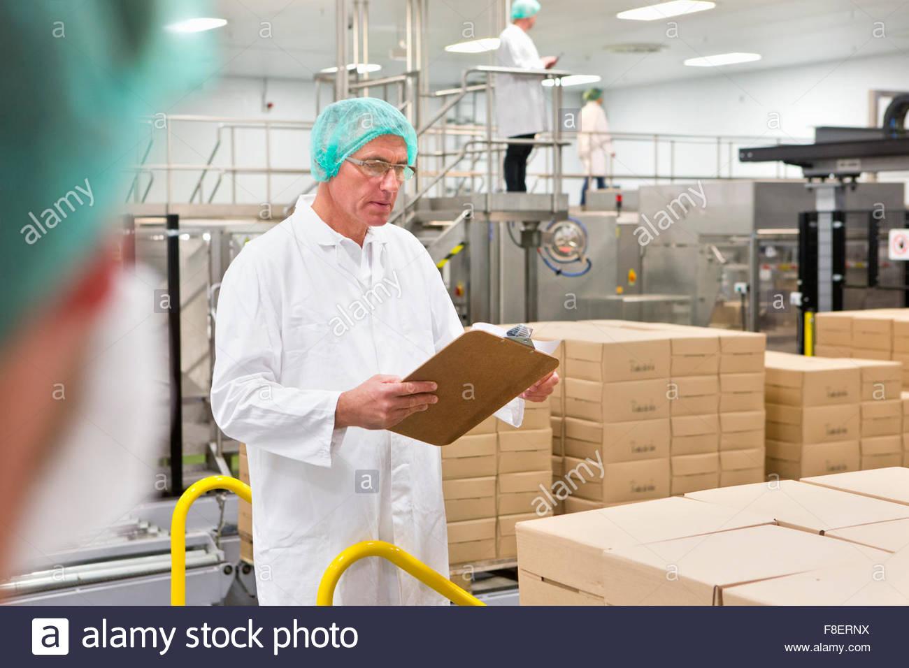 Arbeiter mit Zwischenablage an Lebensmittel Verpackung Produktionslinie Stockbild