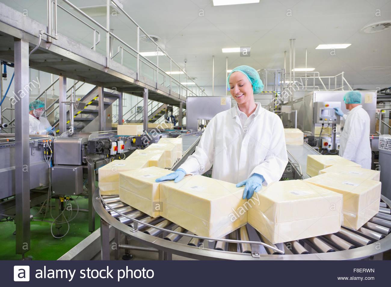 Arbeiter mit großen Blöcken von Käse am Fließband in die Aufbereitungsanlage Stockbild