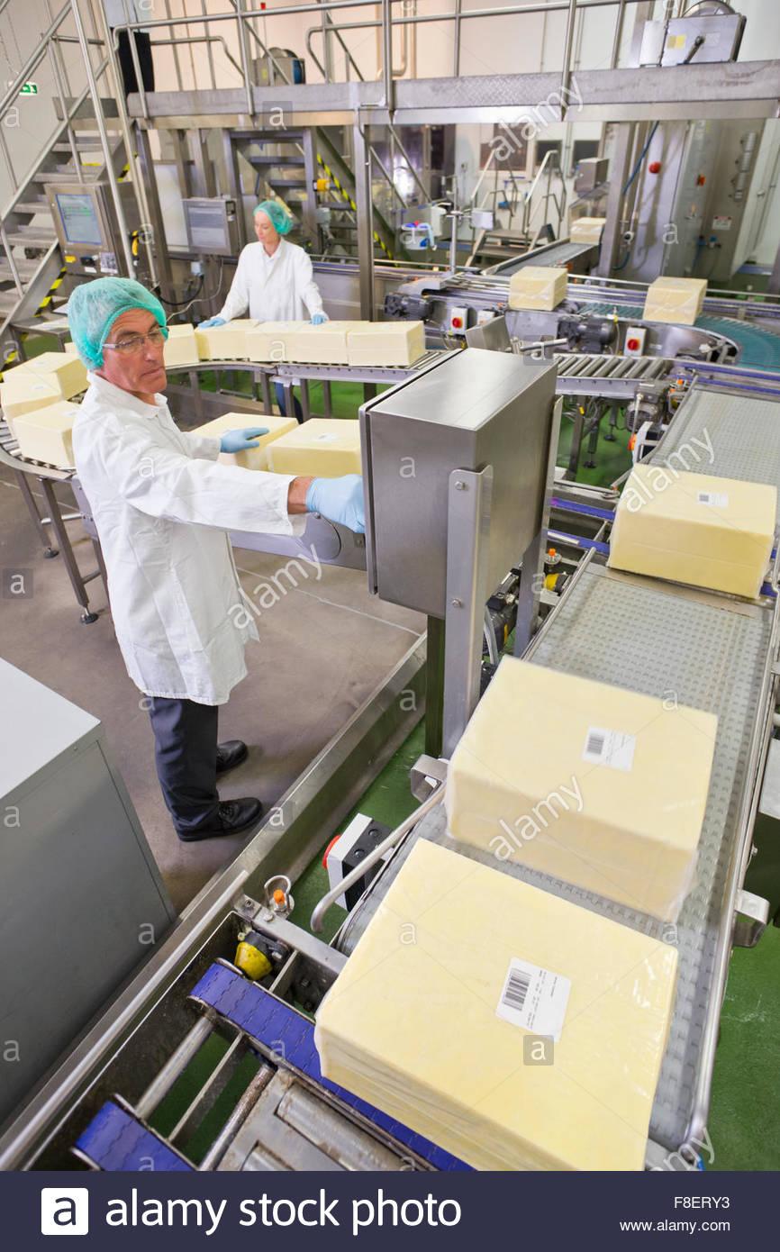 Arbeiter am Fließband Bedienfeld im Käse Verarbeitungsanlage Stockbild
