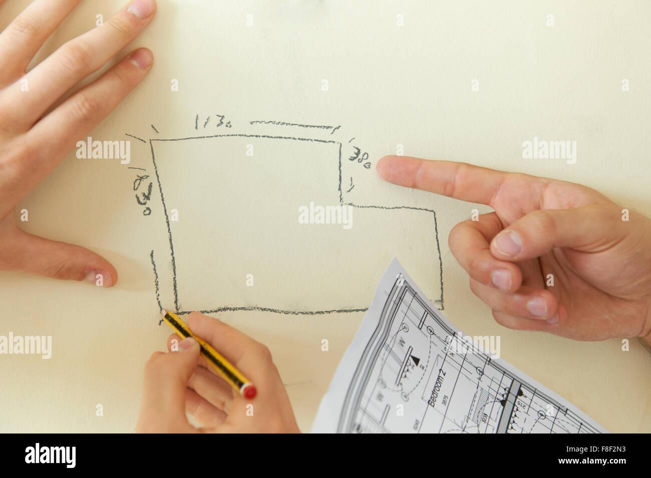 Bauherren suchen zur Hand gezeichneten Plan an Wand Stockbild