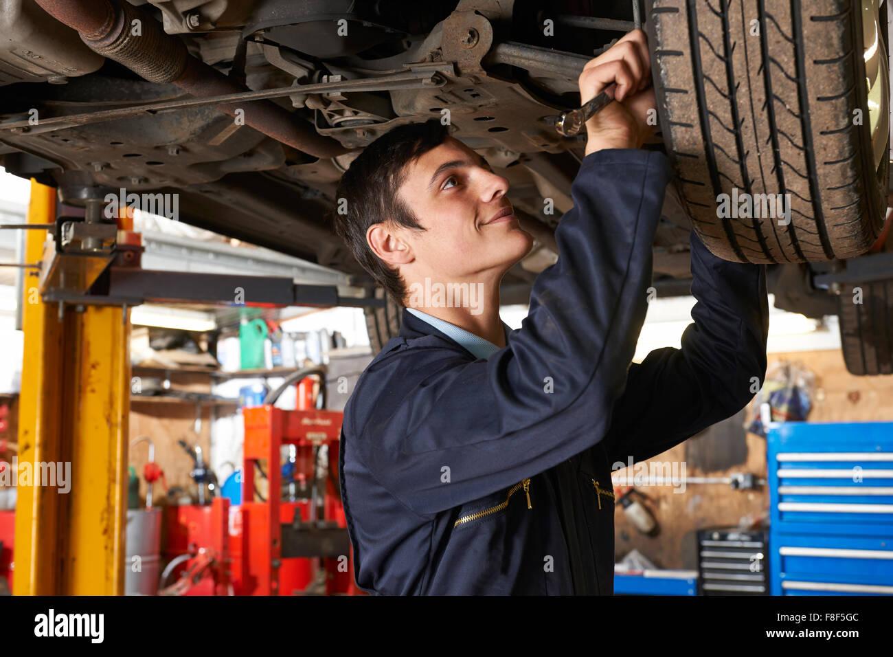 Auszubildende Mechaniker arbeiten unter dem Auto Stockbild