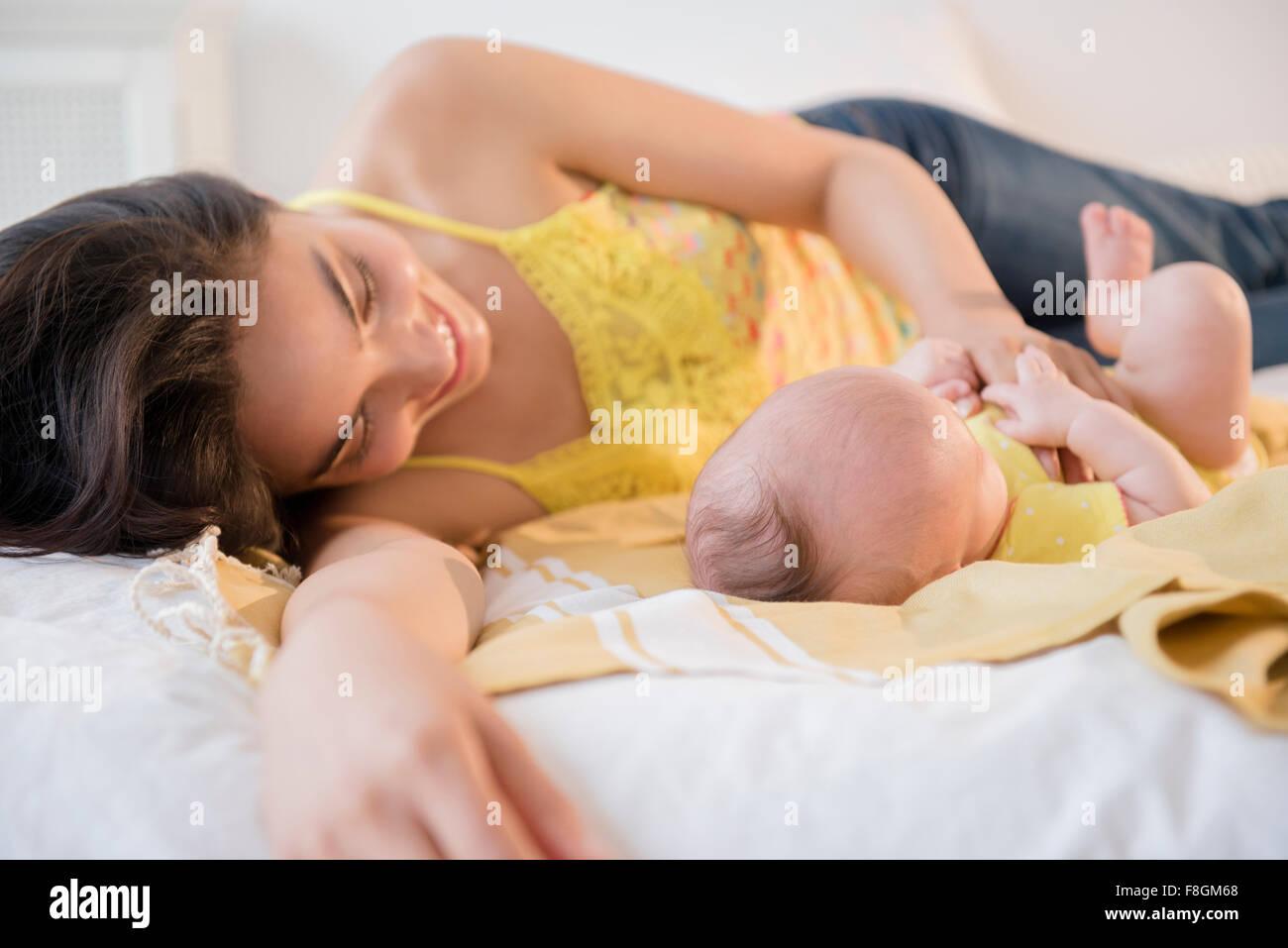 Mutter mit Tochter auf Bett spielen Stockfoto