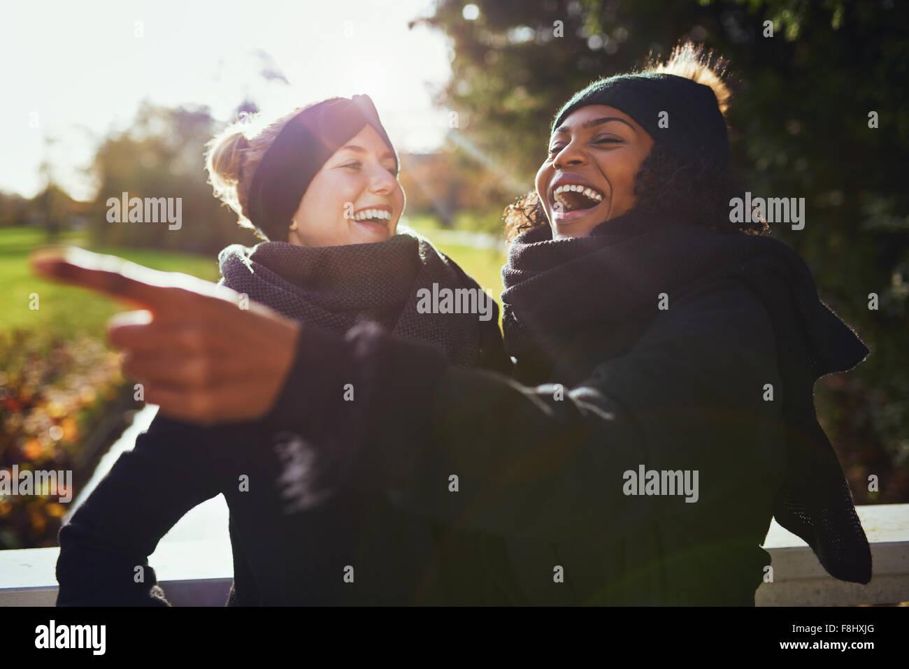 Zwei Frauen lachten etwas stehend im park Stockbild
