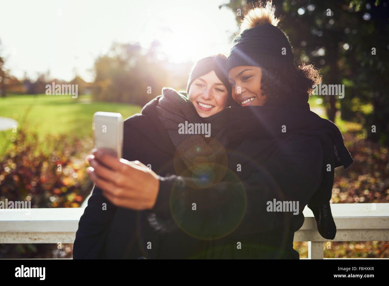 Zwei lächelnde junge Frauen, die die Selfie gegen herbstliche Park Stockbild