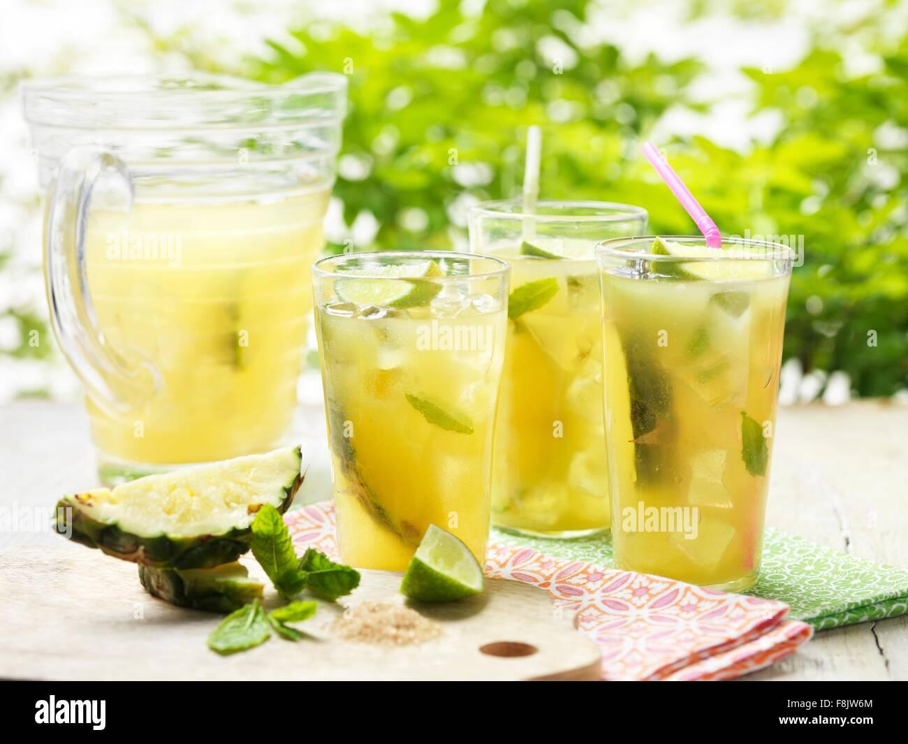 Gläser von hausgemachte golden rum-Punsch mit Kalk, Ananas, Minze ...