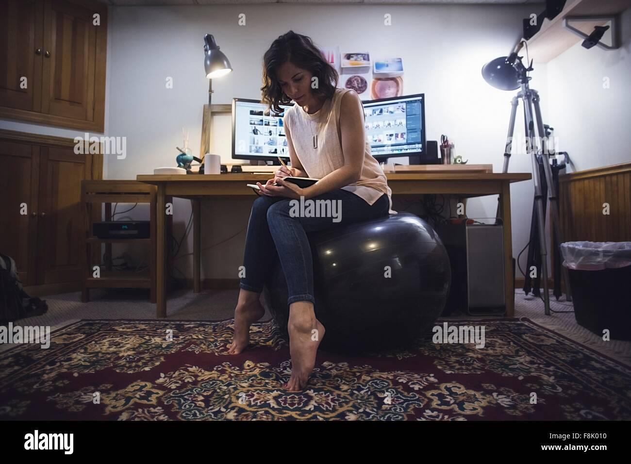 Mitte Erwachsene Frau sitzen auf Yoga-Ball in Tagebuch zu schreiben Stockbild