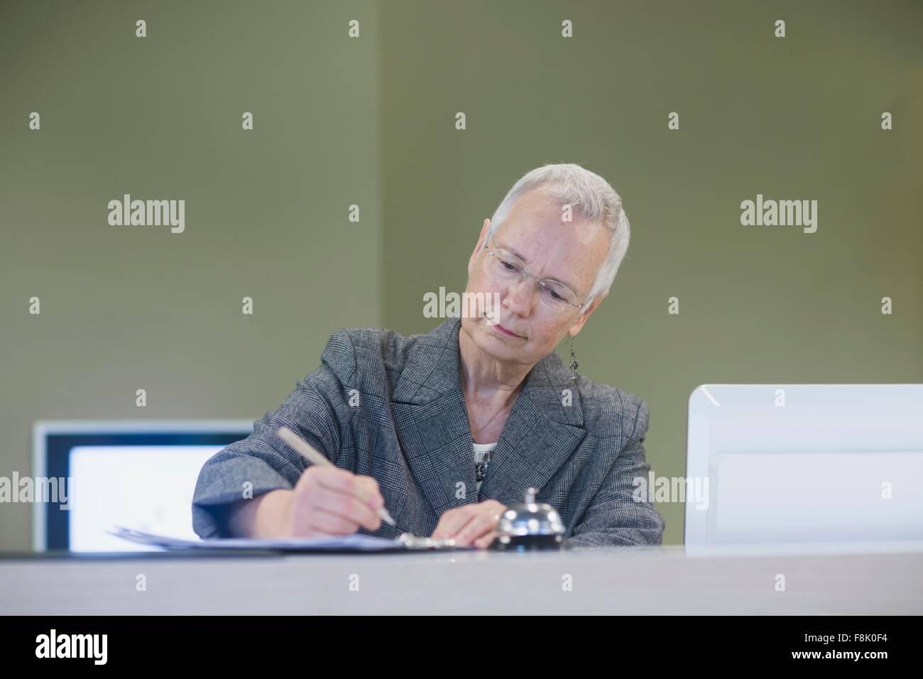 Ältere weibliche Angestellte an der Rezeption schreiben an der Rezeption des Hotels Stockbild