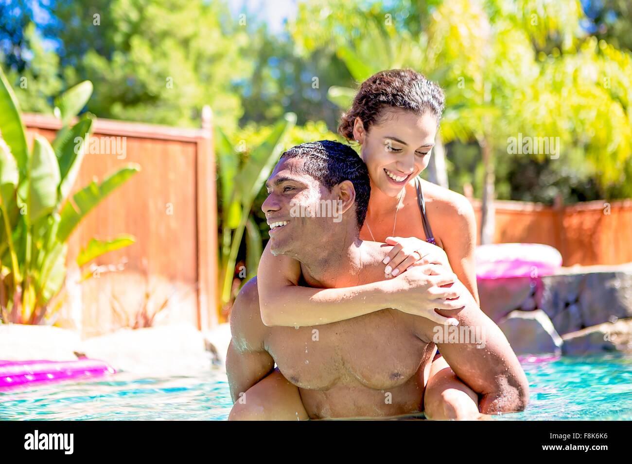 Mitte erwachsener Mann mit junger Frau auf Rücken im Schwimmbad wegsehen lächelnd Stockbild